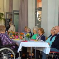Die Senioren setzen sich an die Tische und warten geduldig auf den Beginn.