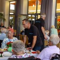 tradition-ES Mitglieder unterhalten sich mit Senioren und servieren das Essen.
